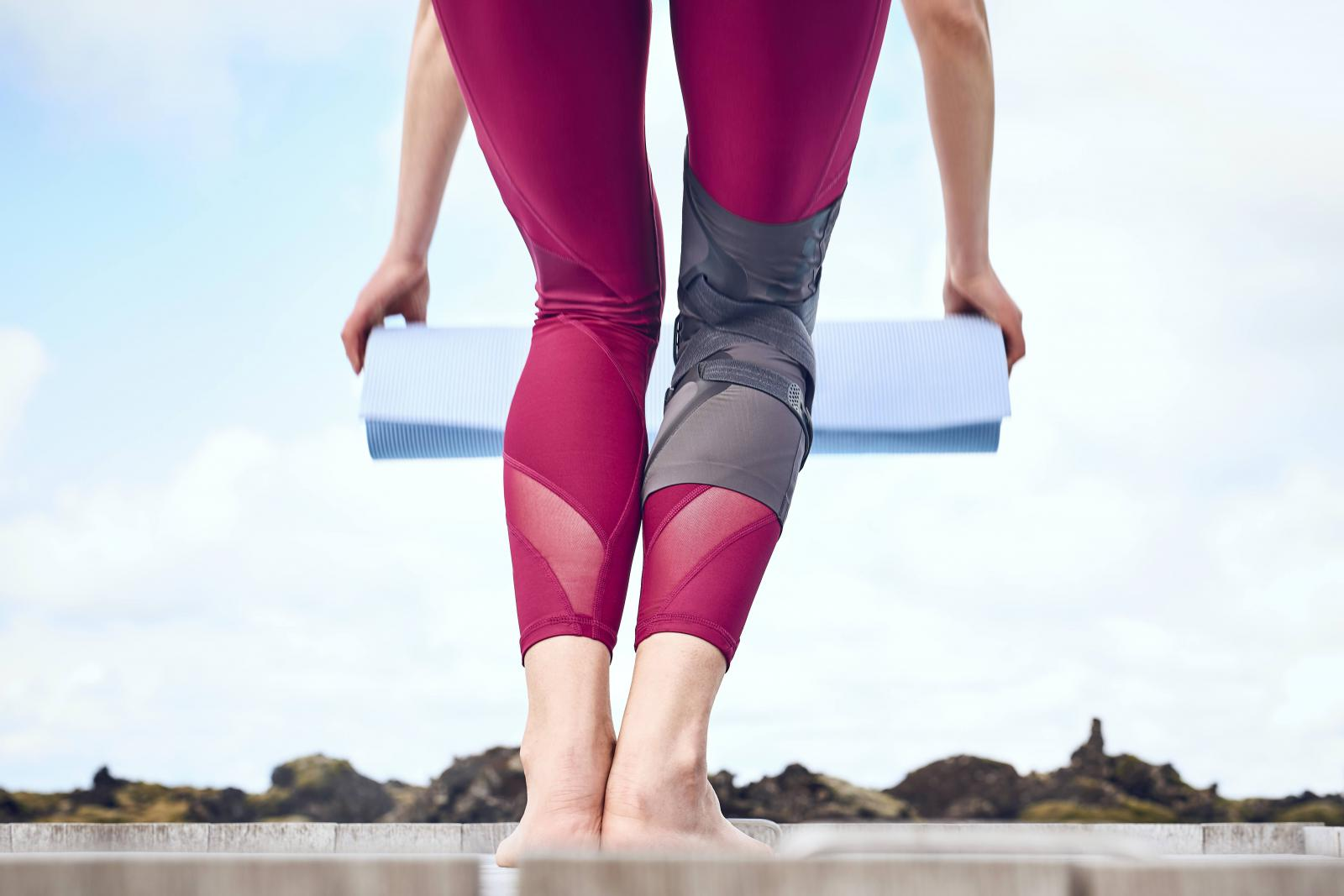 Woman wearing a knee brace rolling out a yoga mat Ossur Unloader One Lite